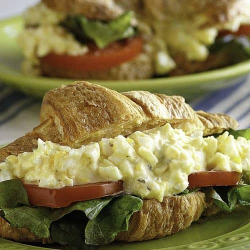 An egg salad sandwich with lettuce and tomato