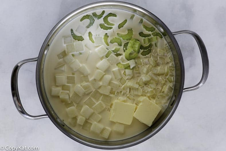 Potato soup cooking, it has butter, celery, potatoes, and more in a large pot.