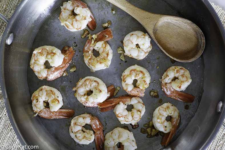 Shrimp cooking in a skllet with butter and garlic.
