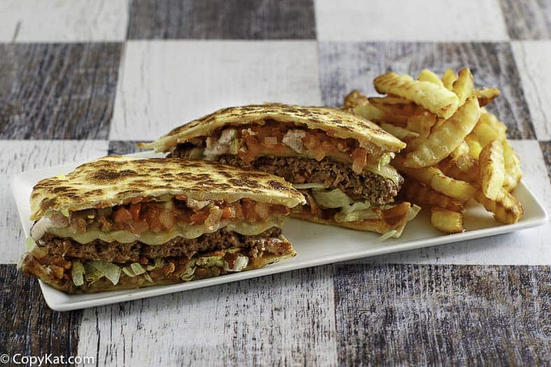 A quesadilla burger cut in half.   Burger has Cheddar cheese quesadilla for the hamburger bun.