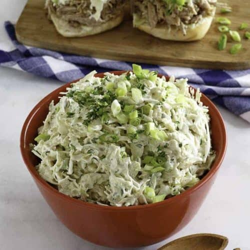Coleslaw served in a bowl, and on pork sandwiches