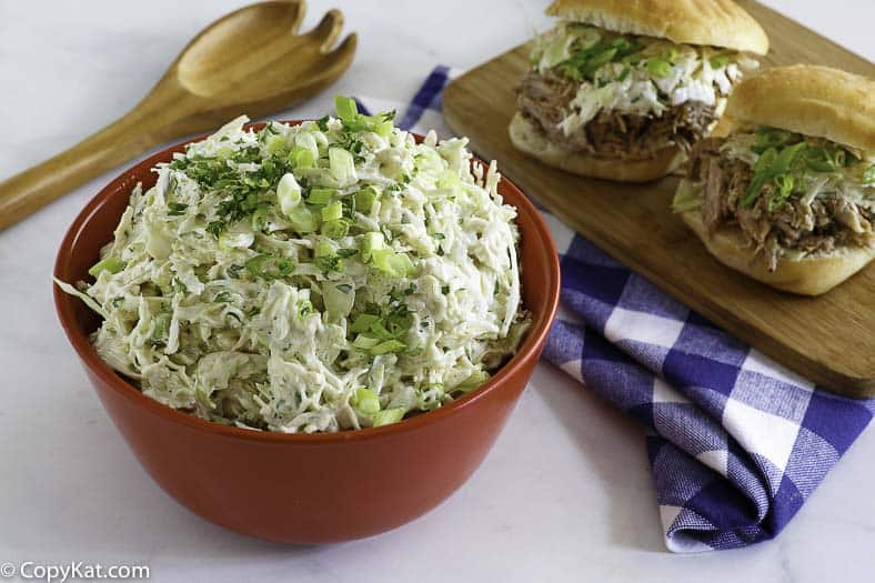 A bowl of homemade Houston's coleslaw next to pulled pork sandwiches