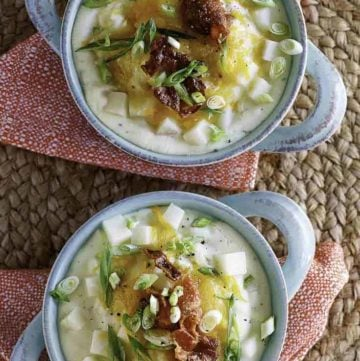two bowls of baked potato soup with toppings of cheese and bacon