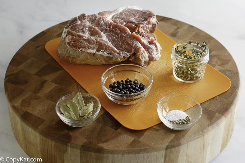 Pictured are pork roast, juniper berries, bay leaves, fresh thyme, salt and pepper.  These are used to make carnitas.