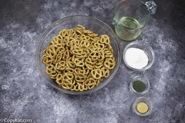 A bowl of pretzels, dry ranch salad dressing mix, garlic powder, vegetable oil, and dill weed.
