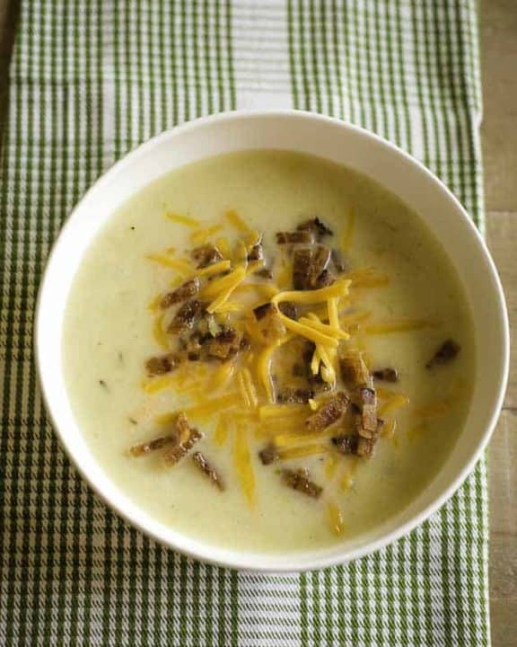 A bowl of creamy country potato soup topped with crispy bacon and shredded Cheddar cheese.
