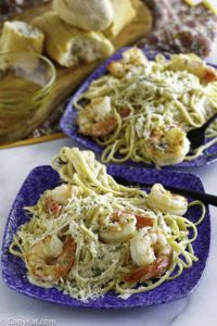 Two plates of homemade copycat Olive Garden shrimp alfredo pasta