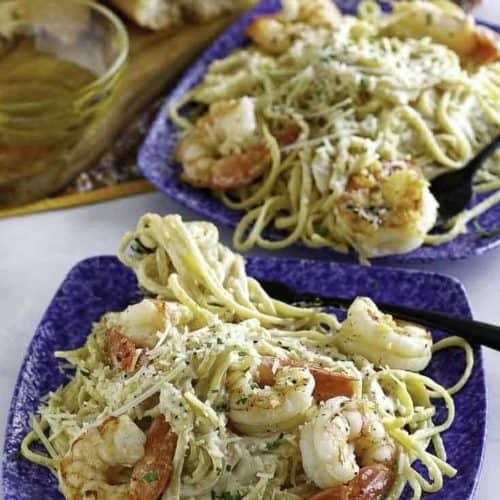 Two plates of shrimp alfredo pasta