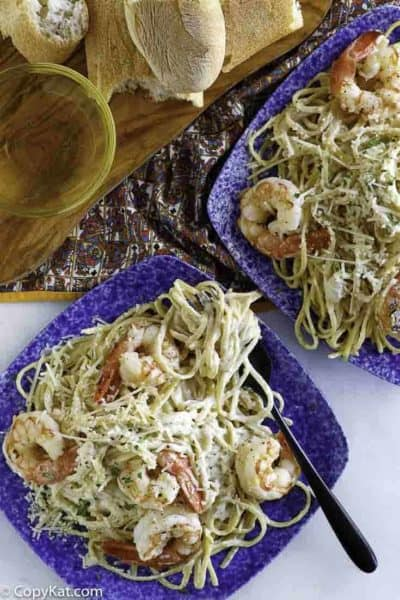 Two plates of homemade copycat Olive Garden shrimp alfredo being served with bread.