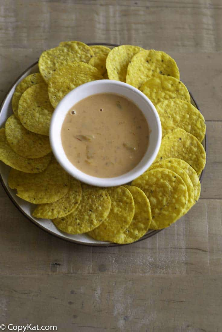 A plate of corn chips with a bowl of creamy peaches and cream salsa