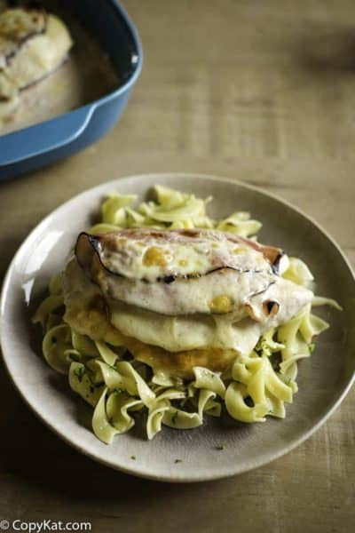 Baked chicken breast stuffed with ham and cheese with mushroom sauce on a bed of noodles