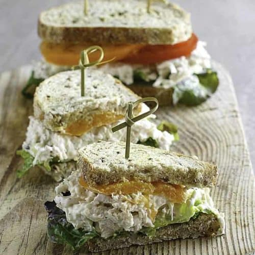 two chicken salad sandwiches on wheat bread with tomatoes and lettuce