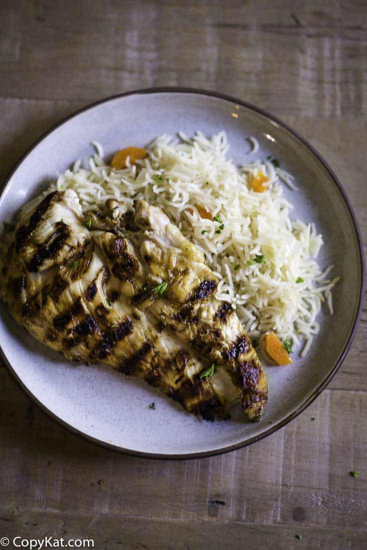 A Chilis Margarita Grilled Chicken breast on a plate with rice pilaf