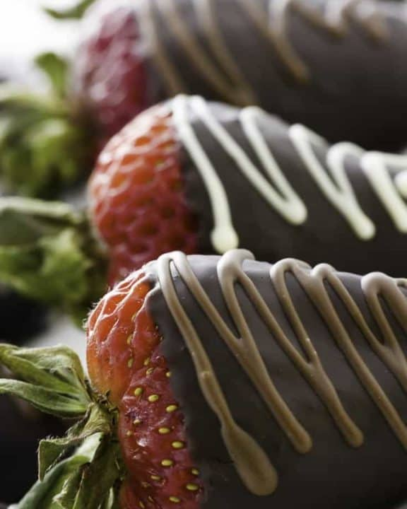 Three chocolate covered strawberries on a plate.