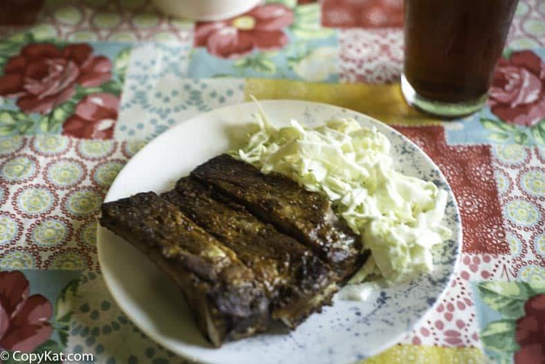 A plate with pork ribs and a sweet and sour coleslaw made with heavy cream.