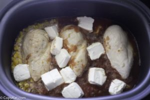 Adding cream cheese to the crockpot of chicken and black beans and corn