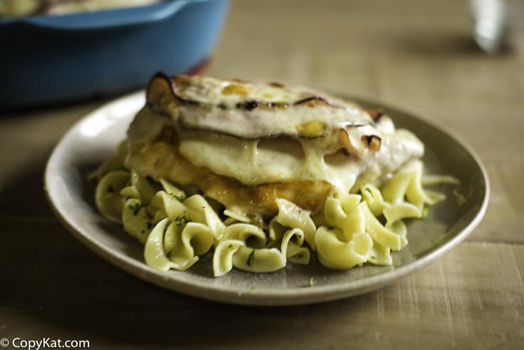 A chicken breast in mushroom sauce stuffed with ham and cheese on a bed of buttered noodles