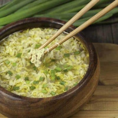 A bowl of egg drop soup and green onions.
