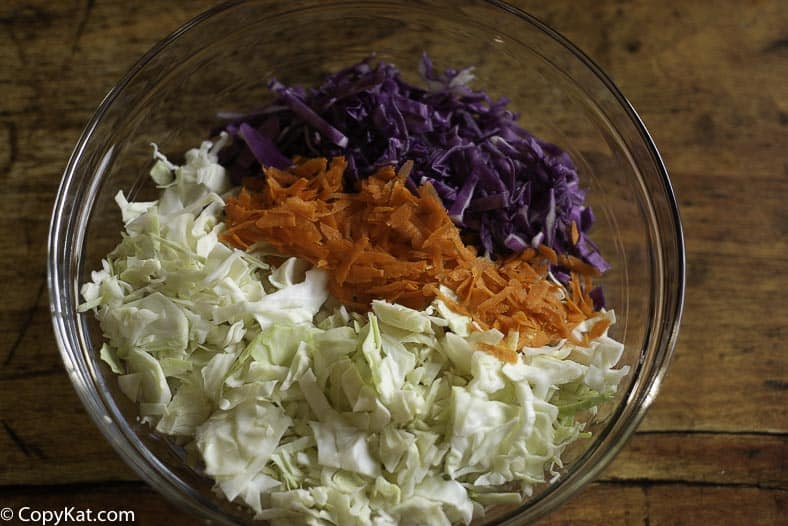 A bowl of shredded green cabbage, red cabbage, and shredded carrots.