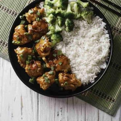 A plate of General Tso's chicken with rice and broccoli.
