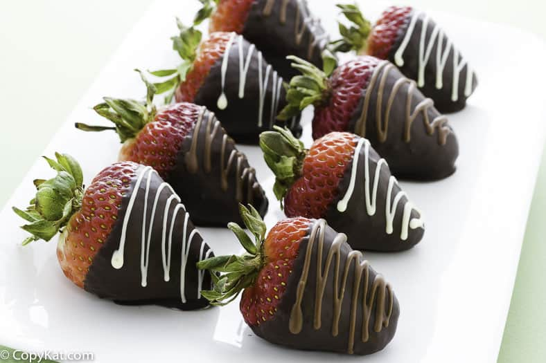 Chocolate covered strawberries on a plate, with chocolate drizzle on them