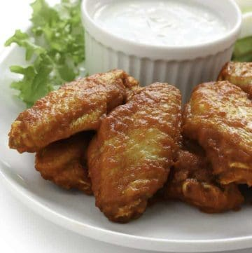 Homemade Junior's Buffalo wings and blue cheese salad dressing on a plate