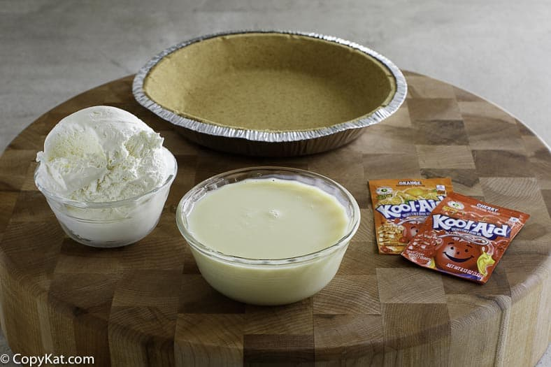 Ingredients for kool aid pie, Cool Whip, Kool Aid, Sweetened Condensed Milk, and a pie shell