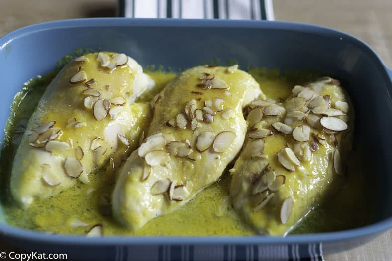 A baking dish with three oven baked lemon sunshine chicken breasts.