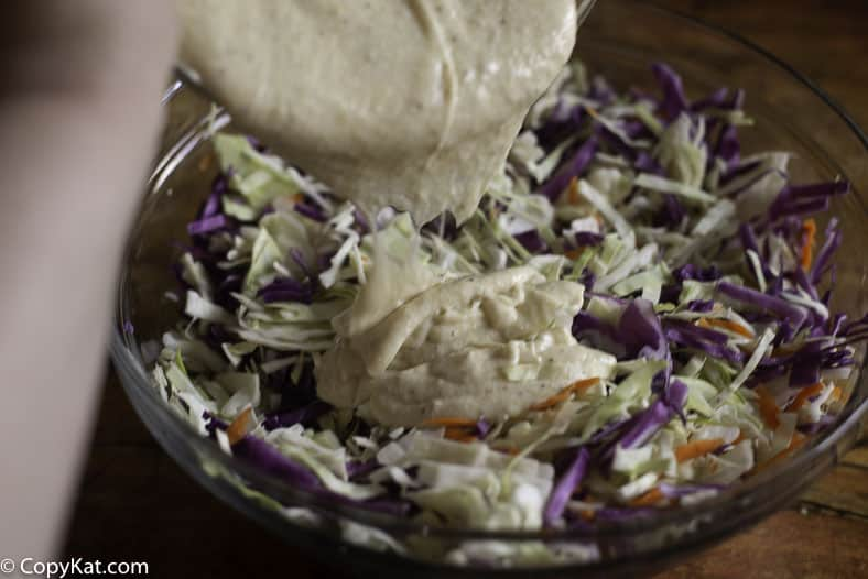 Pouring coleslaw dressing on shredded cabbage