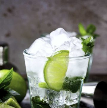 A mojito in a small glass with fresh limes and mint.