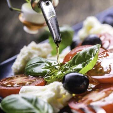 A plate of fresh mozzarella, tomatoes, basil leaves, and olive oil