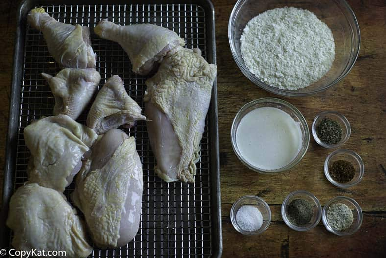 A cut up chicken, potato flakes, and seasonings to make baked chicken