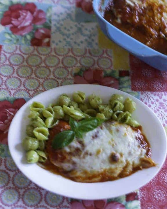 Baked chicken parmesan with cheese served with pesto pasta.