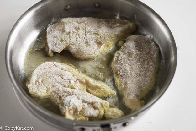 chicken dredged in flour and sauteing in a pan
