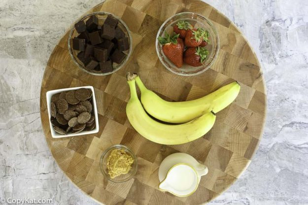 Ingredients for chocolate fondue recipe: milk chocolate, cream, fruit, and more