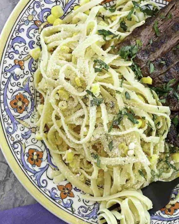 fettuccine pasta salad and steak on a plate