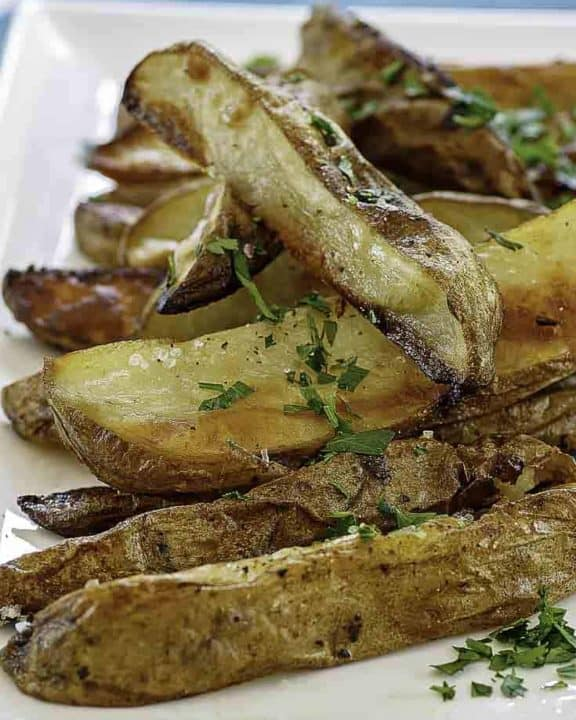 a plate of roasted potatoes with herbs