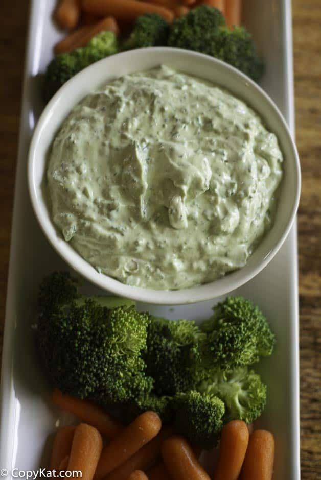 A bowl of green goddess dip and fresh vegetables on a platter.