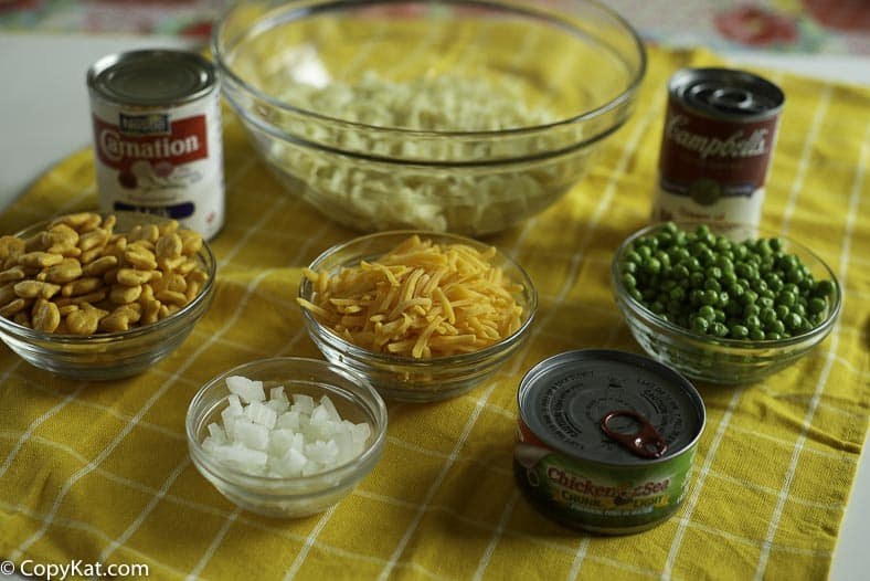 egg noodles, English peas, evaporated milk, fish crackers, onions, and cheese are pictured here.