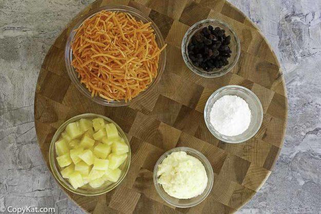 Ingredients to make carrot raisin salad. Shredded Carrots, pineapple, powdered sugar, mayonnaise, and raisins.