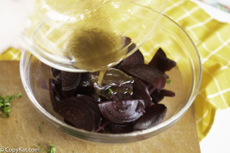 Pouring marinade on beets to make a cold beet salad.