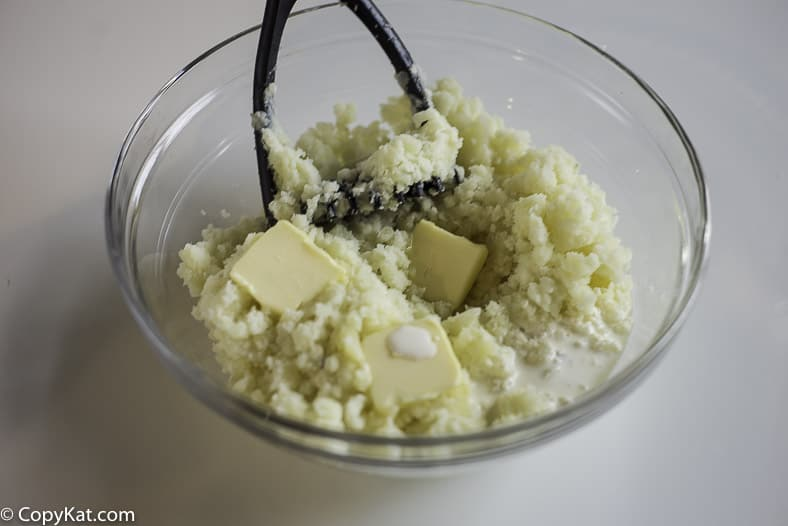 a bowl of potatoes getting mashed with butter, cream, and salt