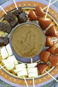 a bowl of chocolate fondue and fruit skewers on a platter.