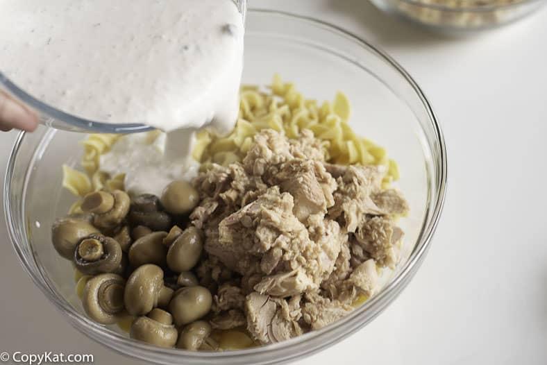 mixing together mushroom sauce, noodles, mushrooms, and tuna