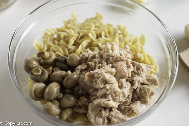 A bowl of extra wide egg noodles, canned tuna, and mushrooms