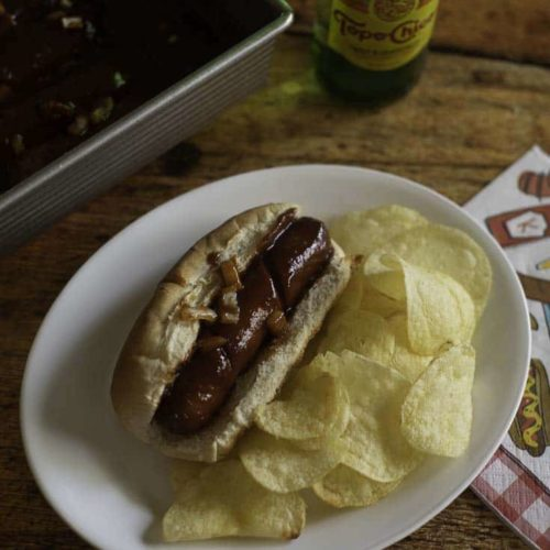 Hot dog baked in the oven with barbecue sauce and onions