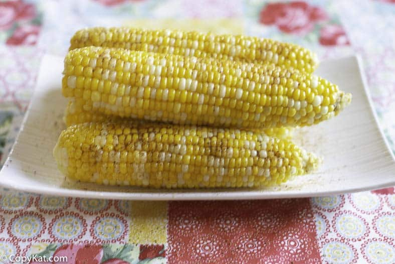Fresh corn has been boiled and topped with butter and old bay seasoning