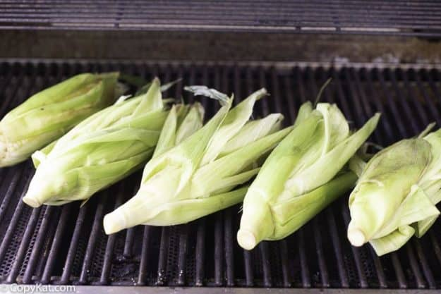 fresh corn being grilled on a hot grill