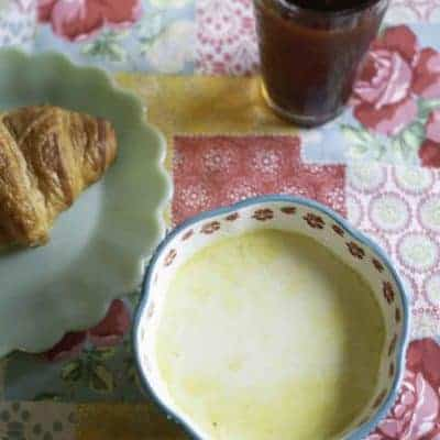 Cream of vegetable soup in a bowl, and a croissant.