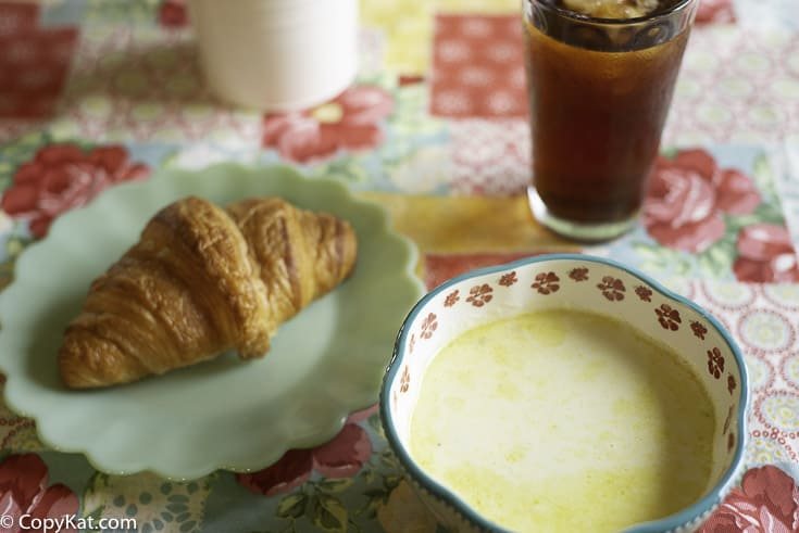 a bowl of cream of vegetable soup by a croissant on a plate